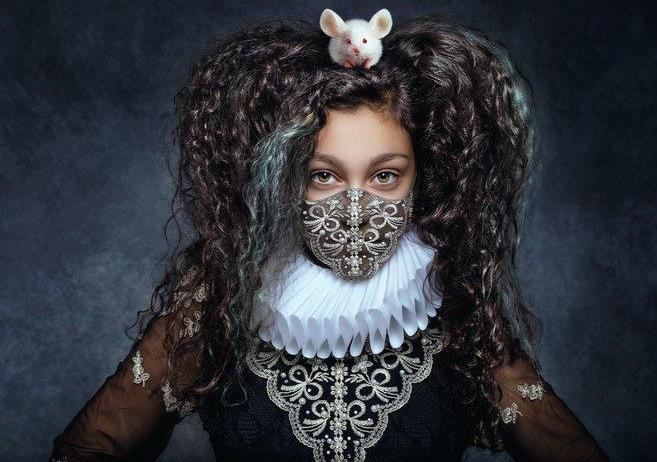 Frau mit schwarzen Harren und weißer Maus auf dem Kopf sowie Kleidung aus dem Mittelalter