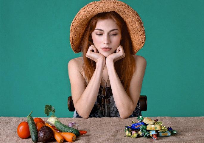 Frau schielt auf Süssigkeiten-Häufchen neben einem Gemüse-Häufchen