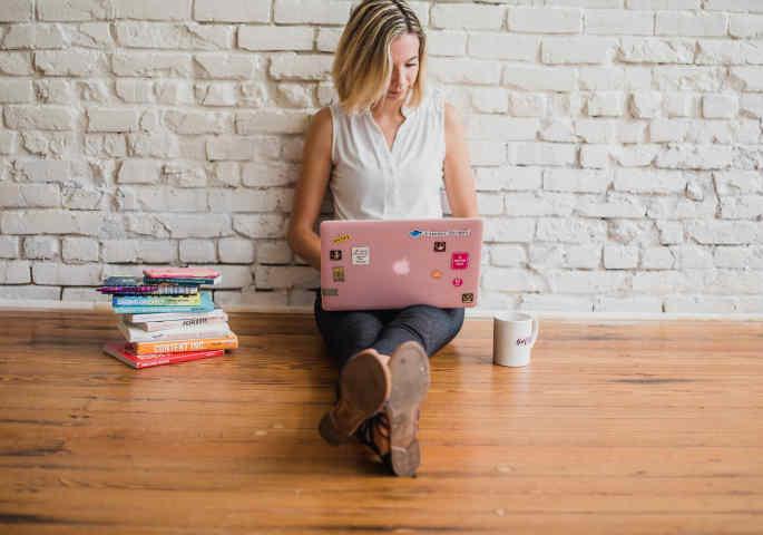 Junge Frau mit Laptop sitzt neben Bücherstapel und Kaffetasse auf dem Boden