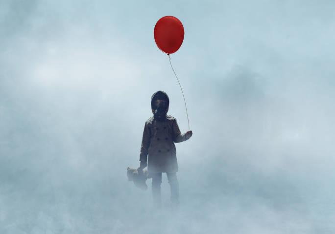 Kind mit Gasmaske steht mit rotem Ballon und Teddy in dichtem Nebel.